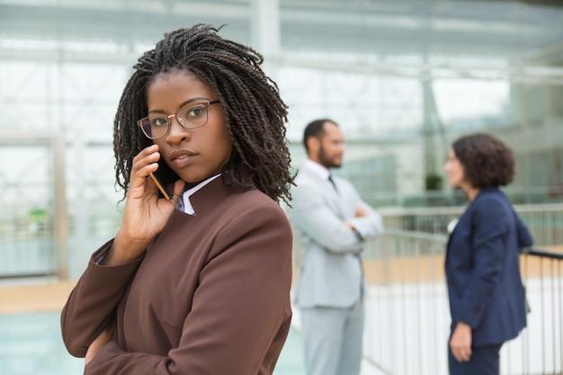 Parlare professionale serio pensieroso sul telefono cellulare