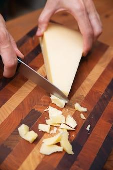 Parmigiano di taglio della donna sul bordo di legno