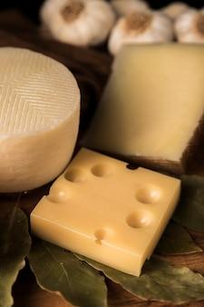 Parmigiano e formaggio emmental con foglie di alloro sul tavolo di legno
