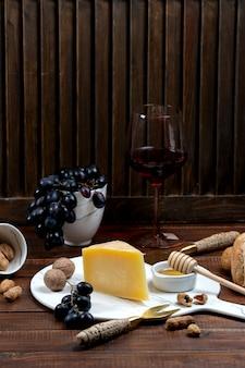 Parmigiano reggiano su tavola di marmo servito con vino e uva