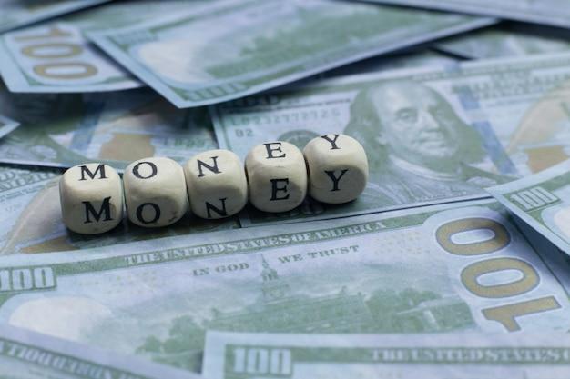 Parola dei soldi sulla banconota del fondo del mattone di legno.