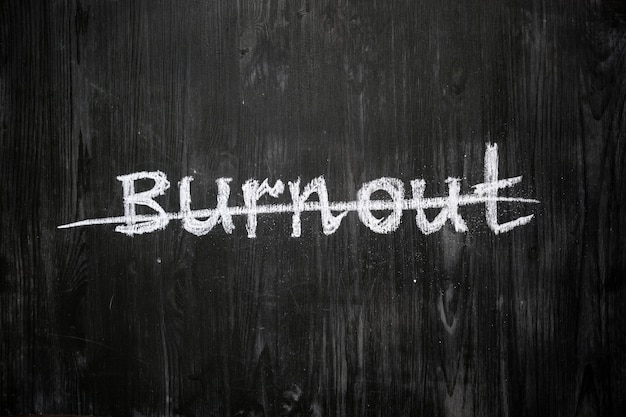 Parola di burnout scritta a mano e barrata sulla lavagna