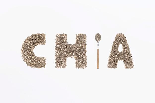 Parola di chia fatta da semi di chia con un cucchiaio pieno di semi su sfondo bianco.