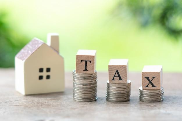 Parola di legno tax e modello casa con pila di monete di orologio a pensare e pianificare.