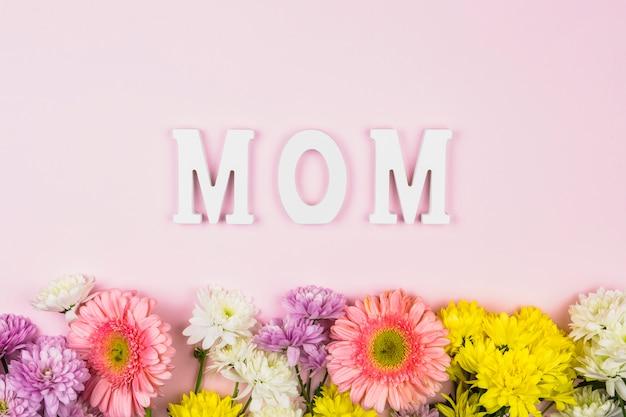 Parola di mamma vicino a fiori freschi luminosi