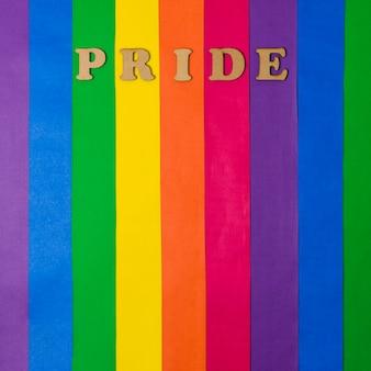 Parola di orgoglio in legno e bandiera lgbt luminosa