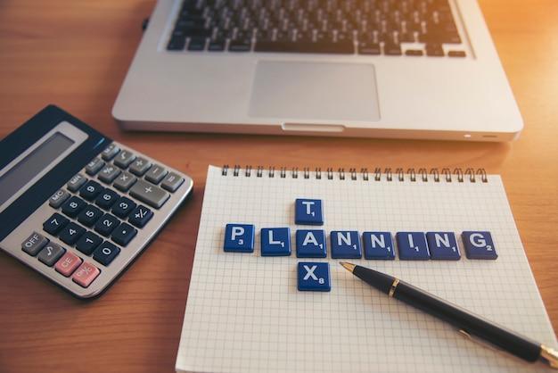 Parola di pianificatore fiscale su carta notebook