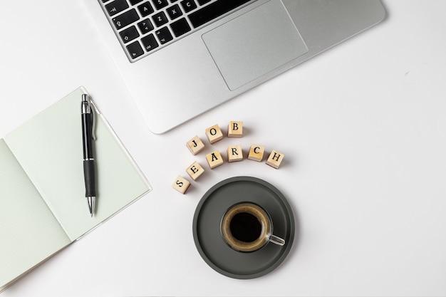 Parola di ricerca di lavoro su timbri in gomma, tazza di caffè, tastiera, penna, blocco note, disoccupazione su grigio