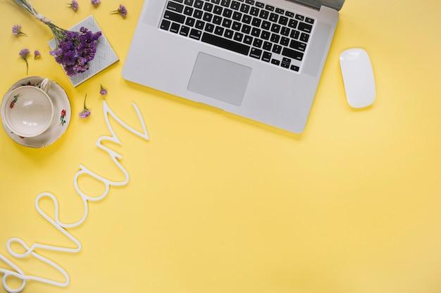 Parola di sogno vicino al computer portatile e tazza vuota sulla superficie gialla