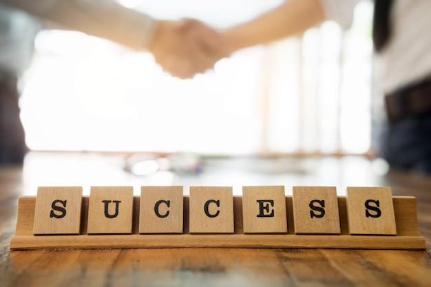 Parola di successo sul tavolo di legno con uomo d'affari stringe la mano durante una riunione in ufficio, affrontare, salutare e concetto di partner concetto