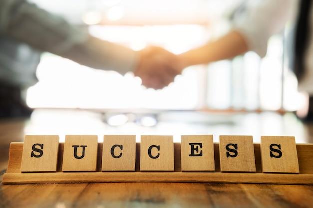 Parola di successo sul tavolo di legno con uomo d'affari stringe la mano durante una riunione in ufficio, trattando, saluto e concetto di partner concetto