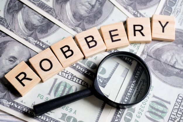 Parola fatta di lettere di legno - rapina, su un grigio con dollari americani accanto a una lente d'ingrandimento. indagine sul crimine.
