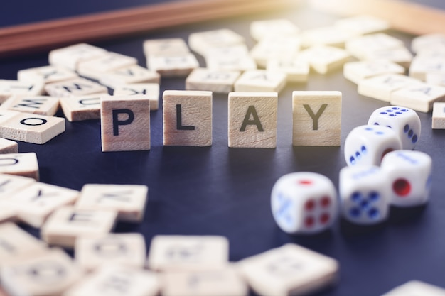 Parola gioca con lettere di legno sul bordo nero con dadi e lettera nel cerchio