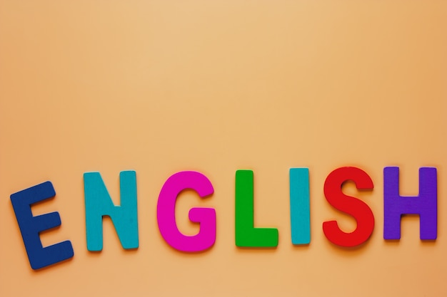 Parola inglese dalle lettere di legno sul fondo di colore beige per l'apprendimento del concetto