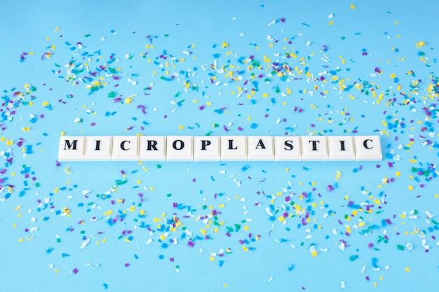 Parola microplastic intorno a piccole particelle di plastica sul blu. microplastica in acqua e alimenti.