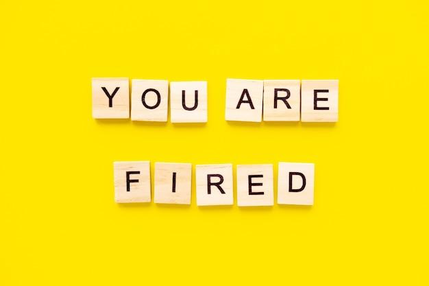 Parole che sei licenziato. blocchi di legno con scritte in cima al tavolo giallo. gestione delle risorse umane e concetto di assunzione e assunzione