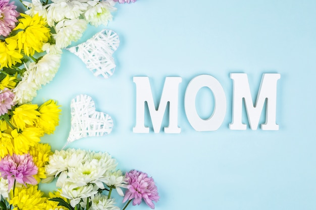 Parole di mamma vicino a cuori e mazzi di fiori freschi