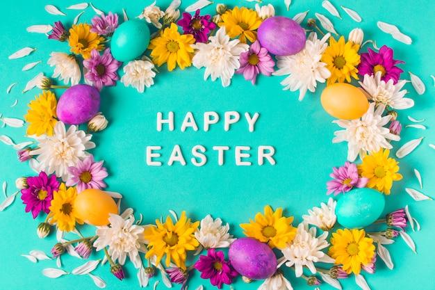 Parole di pasqua felice tra telaio di uova luminose e boccioli di fiori
