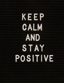 Parole mantieni la calma e rimani positivo sulla lavagna in feltro nero