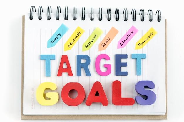 Parole obiettivi bersaglio su notebook su sfondo bianco