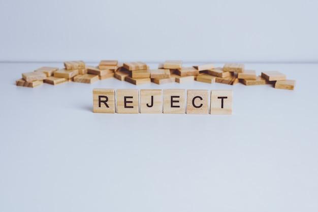 Parole reject fatte con lettere di legno a blocchi. legno abc sul tavolo bianco