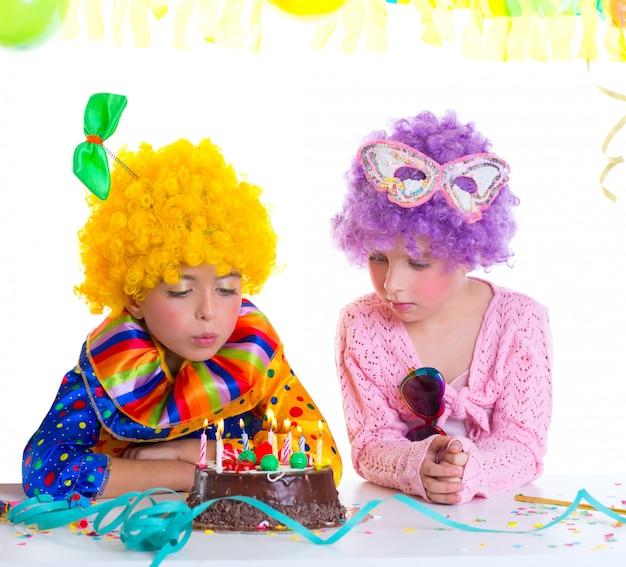 Parrucche del pagliaccio della festa di compleanno dei bambini che soffiano le candele del dolce