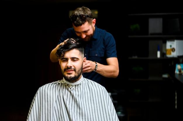 Parrucchiere a tiro medio che taglia i capelli del cliente