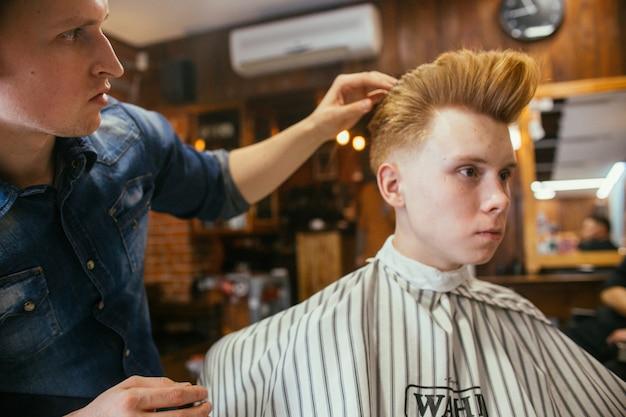 Parrucchiere adolescente di tagli di capelli del ragazzo di redhead nel negozio di barbiere