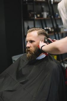 Parrucchiere alla moda taglio dei capelli del cliente al negozio di barbiere.