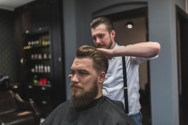 Parrucchiere bello che disegna i capelli del cliente