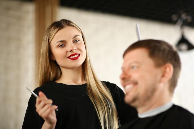 Parrucchiere biondo con cliente uomo in salone