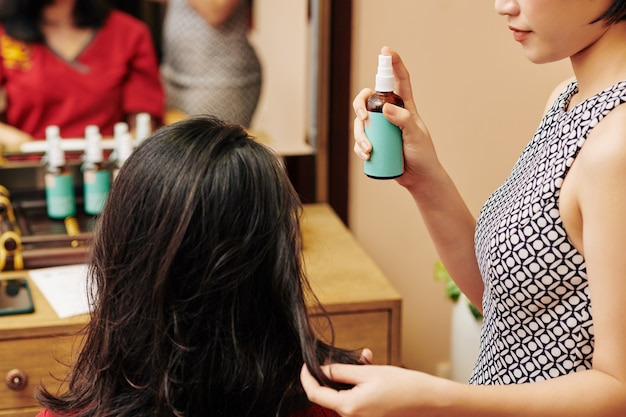 Parrucchiere che applica siero idratante