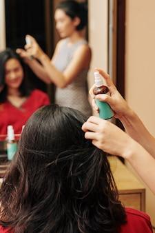 Parrucchiere che applica spray per proteggere dal calore