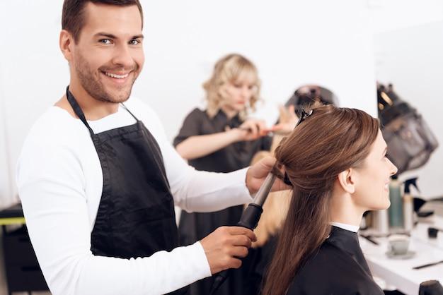 Parrucchiere che arriccia capelli castani di bella donna.