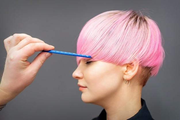 Parrucchiere che controlla breve acconciatura rosa di giovane donna con pettine sul muro grigio