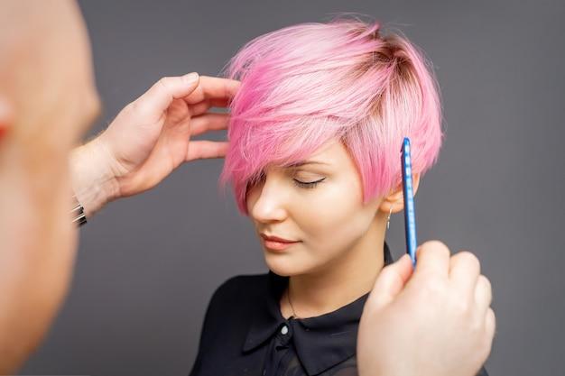Parrucchiere che controlla breve acconciatura rosa di giovane donna sul muro grigio