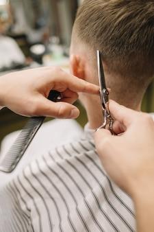 Parrucchiere che dà un taglio di capelli a un cliente
