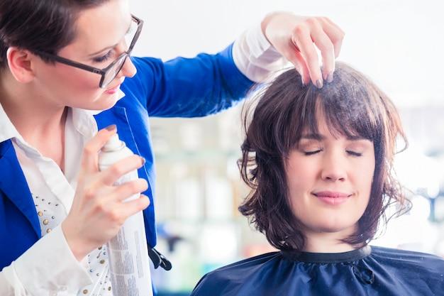 Parrucchiere che disegna i capelli della donna in negozio
