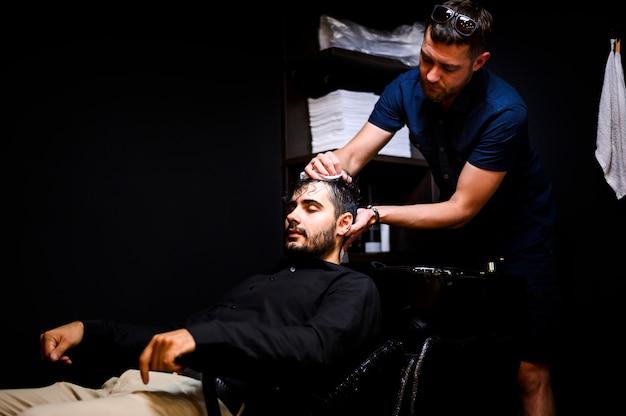 Parrucchiere che lava i capelli del suo cliente