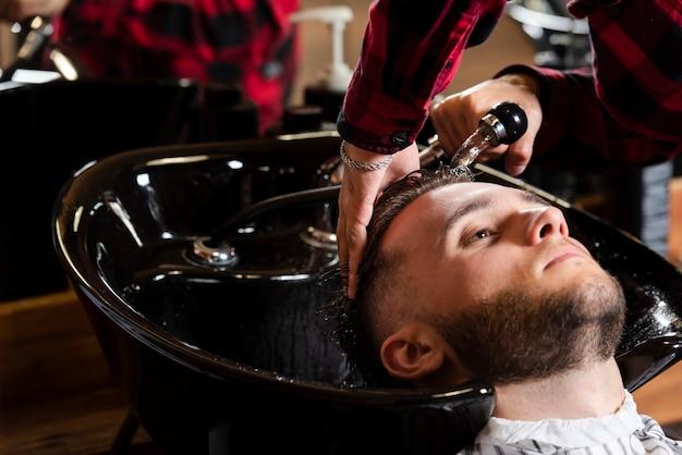 Parrucchiere che lava i capelli di un uomo