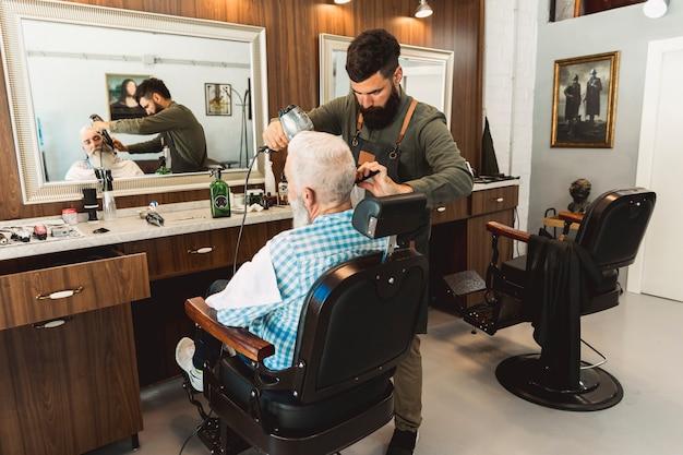 Parrucchiere che pettina e che asciuga capelli del cliente senior
