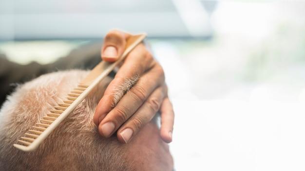 Parrucchiere che pettina i capelli al cliente nel negozio di barbiere
