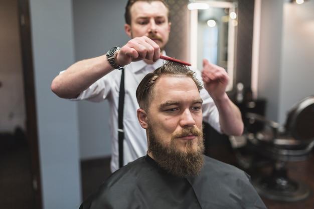 Parrucchiere che pettina i capelli dell'uomo prima del taglio