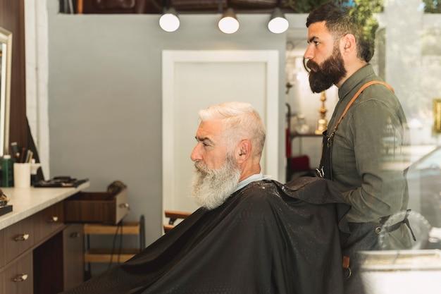 Parrucchiere che prepara per taglio di capelli anziano cliente barbuto