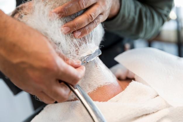 Parrucchiere che rade barba al cliente