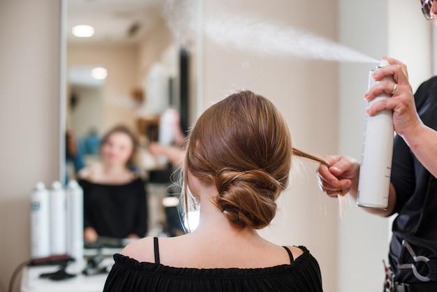 Parrucchiere che ripara i capelli della donna con la lacca per capelli