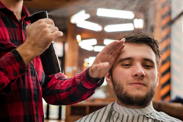 Parrucchiere che spruzza i capelli del cliente