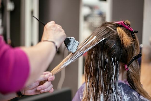 Parrucchiere che tinge i capelli di una donna