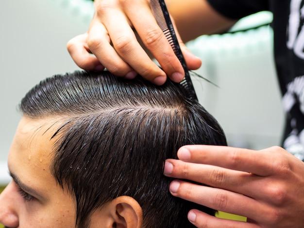 Parrucchiere del primo piano che pettina capelli