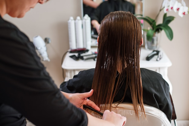 Parrucchiere dello stilista che fa il primo piano di taglio di capelli dell'attrezzatura del lavoro